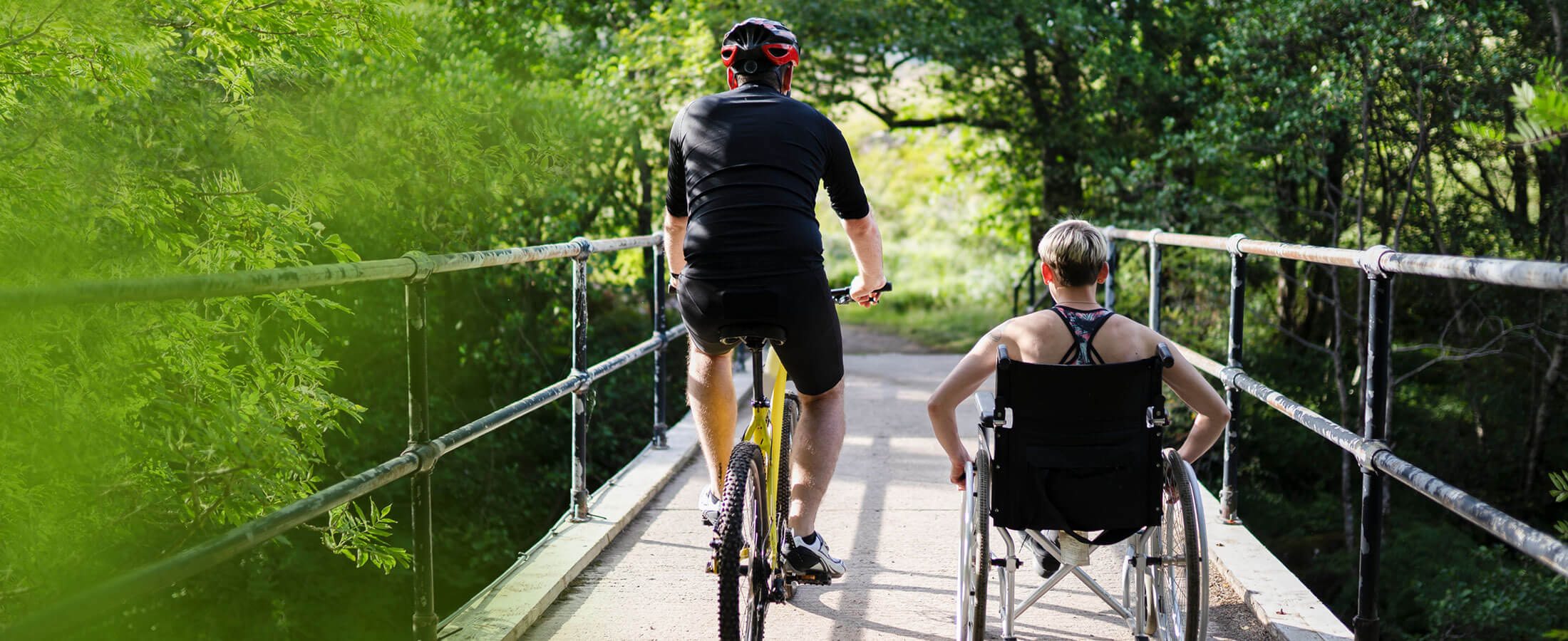 Man on a bike and woman in wheelchair on a bridge in a park